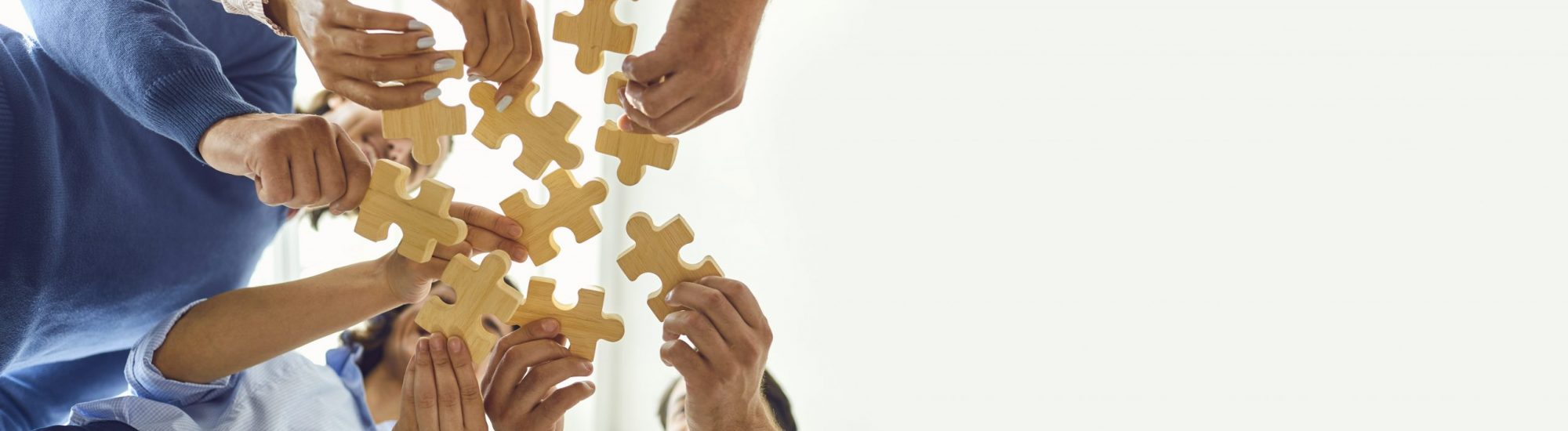 Concept of finding solution. From below of company workers assembling pieces of jigsaw puzzle in work meeting. Banner with happy office employees playing game during team building activity